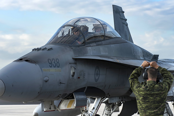 An aviation technician from 425 Tactical Fighter Squadron directs the pilot of a CF-188 Hornet aircraft during CHUMEX at the Homestead Air Reserve Base in Florida, January 31, 2017. Photo: Cpl Jean-Roch Chabot, 3 Wing Bagotville BN02-2017-0036-003
