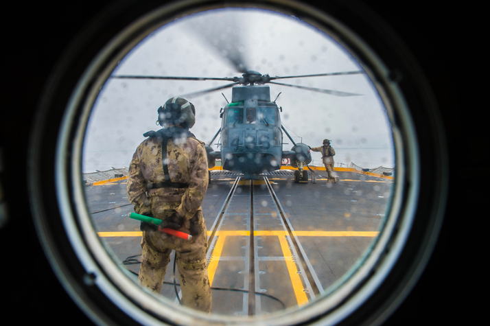 An Aviation Technician from 443 Squadron gets ready to guide a Sea King helicopter attached to Her Majesty's Canadian Ship WINNIPEG for flight training during POSEIDON CUTLASS, March 13, 2017. Photo: Cpl Carbe Orellana, MARPAC Imaging Services ET2017-4005-08