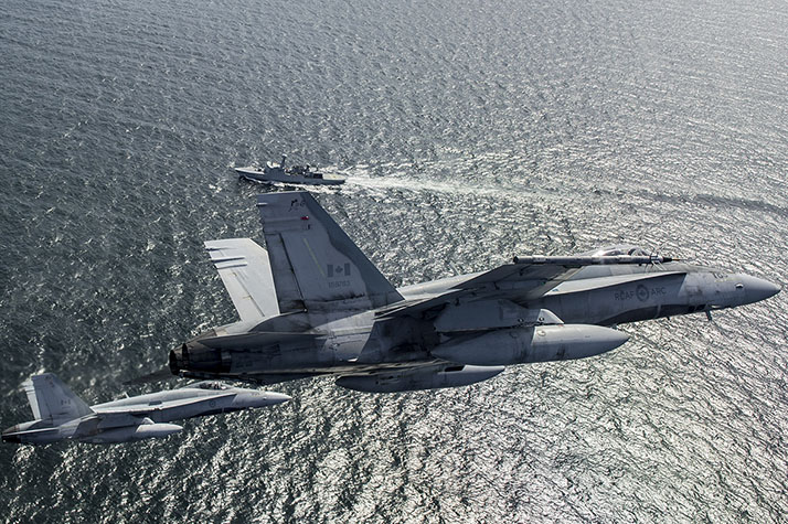 Deux chasseurs CF-188 Hornet de l'Aviation royale canadienne de la Force opérationnelle aérienne (FOA)-Islande participent à un exercice interarmées avec le HDMS Vaedderen, une frégate de la marine royale danoise en patrouille dans l'Atlantique Nord, le 5 juin 2017, au cours de l'opération REASSURANCE. Photo : Pilote de l'Aviation royale canadienne, MDN RP09-2017-0031-006