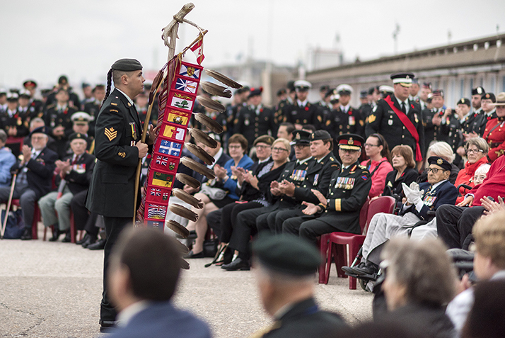 Sergeant Moogly Tetrault-Hamel (left) carries the Canadian Armed Forces Eagle Staff at the Indigenous Sunrise Ceremony in honour of the 75th anniversary of the Dieppe Raid in Dieppe, France on August 18, 2017. Photo: Cpl Andrew Wesley, Directorate of Army Public Affairs LF03-2017-0152-012