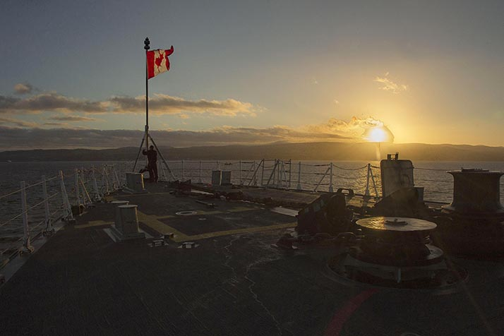 A crewmember onboard Her Majesty's Canadian Ship (HMCS) CHARLOTTETOWN raises the Jack during the Colours ceremony while at anchor off the coast of Scotland during Operation REASSURANCE, October 6, 2016. Photo: Cpl Blaine Sewell, Formation Imaging Services RP10-2016-0082-007