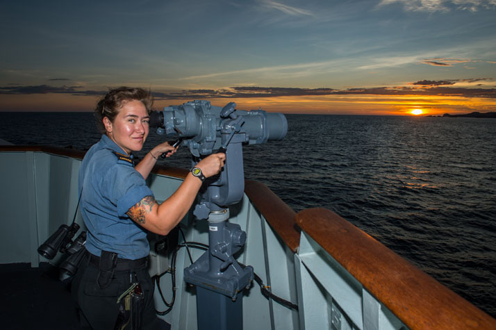 Leading Seaman Kayla Ruiz uses the Big Eyes on Her Majesty's Canadian Ship (HMCS) WINNIPEG as the ship departs the Philippines, April 18, 2017. Photo: Cpl Carbe Orellana, MARPAC Imaging Services ET2017-4033-07