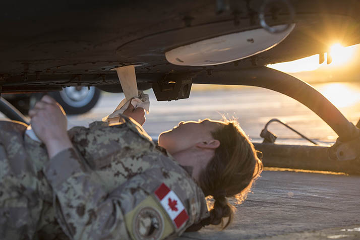 A Canadian Armed Forces Avionics Systems Technician inspects and cleans a CH-146 Griffon helicopter at Camp Érable, Iraq during Operation IMPACT. Photo: Op Impact, DND KW06-2017-0122-014