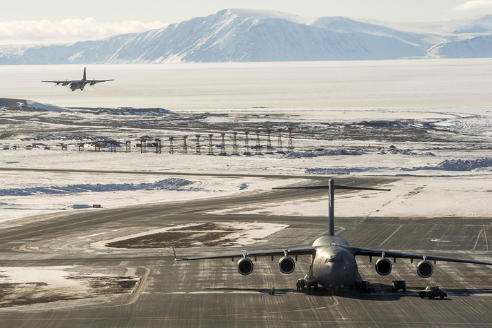 A CC-177 Globemaster aircraft sits on the runway as CC-130 Hercules aircraft approaches, in Thule, Greenland during Operation BOXTOP on April 24, 2017. Photo: Corporal Audrey Solomon, 8 Wing Imaging TN02-2017-0144-061
