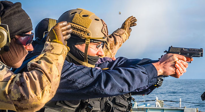 Maritime Tactical Operations Group (MTOG) Tiger Team and Royal Canadian Navy Ship's Boarding Party members conduct pistol training on the flight deck of Her Majesty's Canadian Ship (HMCS) St. John's during Operation REASSURANCE, off the Norwegian coast on February 21, 2018.