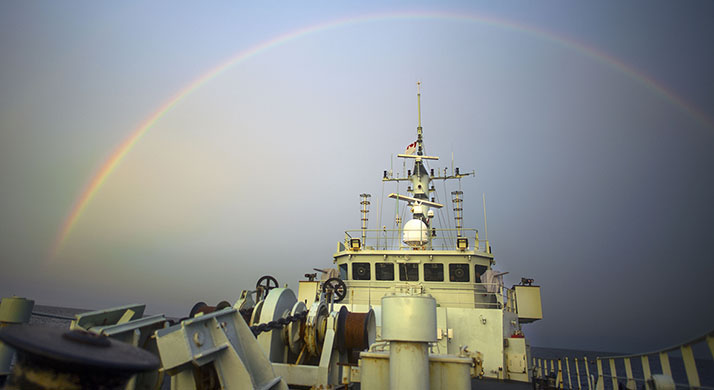 Her Majesty's Canadian Ship KINGSTON sails under an early morning rainbow off the coast of West Africa  during Operation PROJECTION on March 26, 2018. Photo credit: Sgt Shilo Adamson, Canadian Forces Recruiting Group Headquarters, CFB Borden. RG2018-0030-01