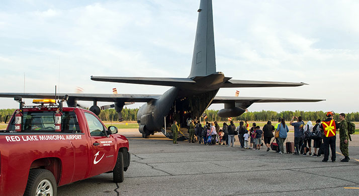 Evacuees from Red Lake, Ontario affected by the forest fires in Northern Manitoba board a CC-130H Hercules aircraft from 435 Transport and Rescue Squadron bound for Winnipeg, Manitoba during Operation LENTUS on May 23, 2018.