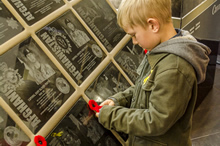 Calgary, Alberta 25 August 2014 – William Nathan Herbert, age 6, the nephew of Cpl Nathan Hornburg, places a poppy on his uncle's plaque at the Afghanistan Memorial Vigil displayed at the Calgary Tower. Photo by Sgt Brangwyn Jones, 41 Canadian Brigade Group