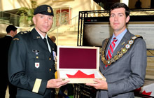 Edmonton, AB. 11 August 2014 – Brigadier-General W. Eyre, Commander 3rd Canadian Division (3 Cdn Div) presents His Worship Don Iveson, Mayor City of Edmonton, with a Canadian Flag that was flown in Afghanistan during the Canadian mission following the Afghanistan Memorial Vigil Commemoration Ceremony held at Edmonton City Hall on August 11, 2014. The Vigil consists of 192 plaques and honours the bravery and dedication of those who fell during operations in Afghanistan. The display was formerly part of the Kandahar Air Field cenotaph and is travelling across Canada and the USA. (Image by : MCpl VanPutten, 3 CDSG Imaging)
