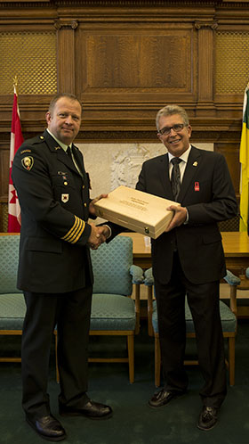 Regina, Saskatchewan.  2 September 2014 – 38 CBG Commander Colonel Ross Ermel presents the Deputy Mayor of Regina Bryon Burnett a Canadian flag that was flown in Afghanistan. (Photo by MCpl Cameron Skrypnyk. Copyright 2014 DND/MDN)
