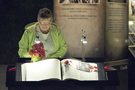 CFB Shilo, Manitoba. 10 September 2014 – A visitor to the CFB Shilo Afghanistan Memorial Vigil (AMV) signs her name to the guest book after perusing the exhibit's memorial plaques following the opening ceremony held the day before. (Photo by Jules Xavier, Shilo Stag)