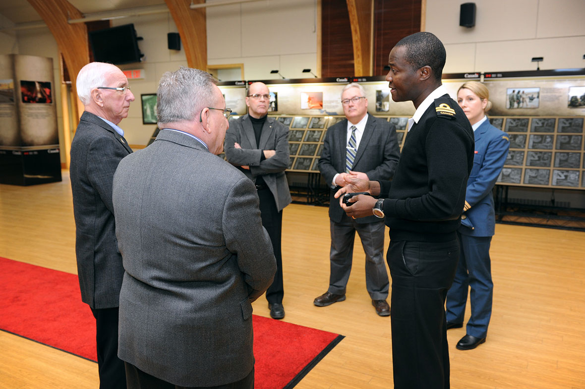 On March 13, 2015, Navy Lieutenant Serge Tsoto (foreground, right), explains the meaning of the Afghanistan Memorial Vigil to the guests: Jacques Patenaude and Lucien Poirier, of Fondation Aérovision Québec (foreground, left to right); Lieutenant-Colonel (Ret'd) Rémi Landry, Professor at the University of Sherbrooke (background, left); Marc Imbeault, Dean of Studies and Research, Royal Military College Saint-Jean (background, centre); Maj Stéphanie Godin (background, right). Photo: Mario Poirier, Multimedia Technician, Royal Military College Saint-Jean