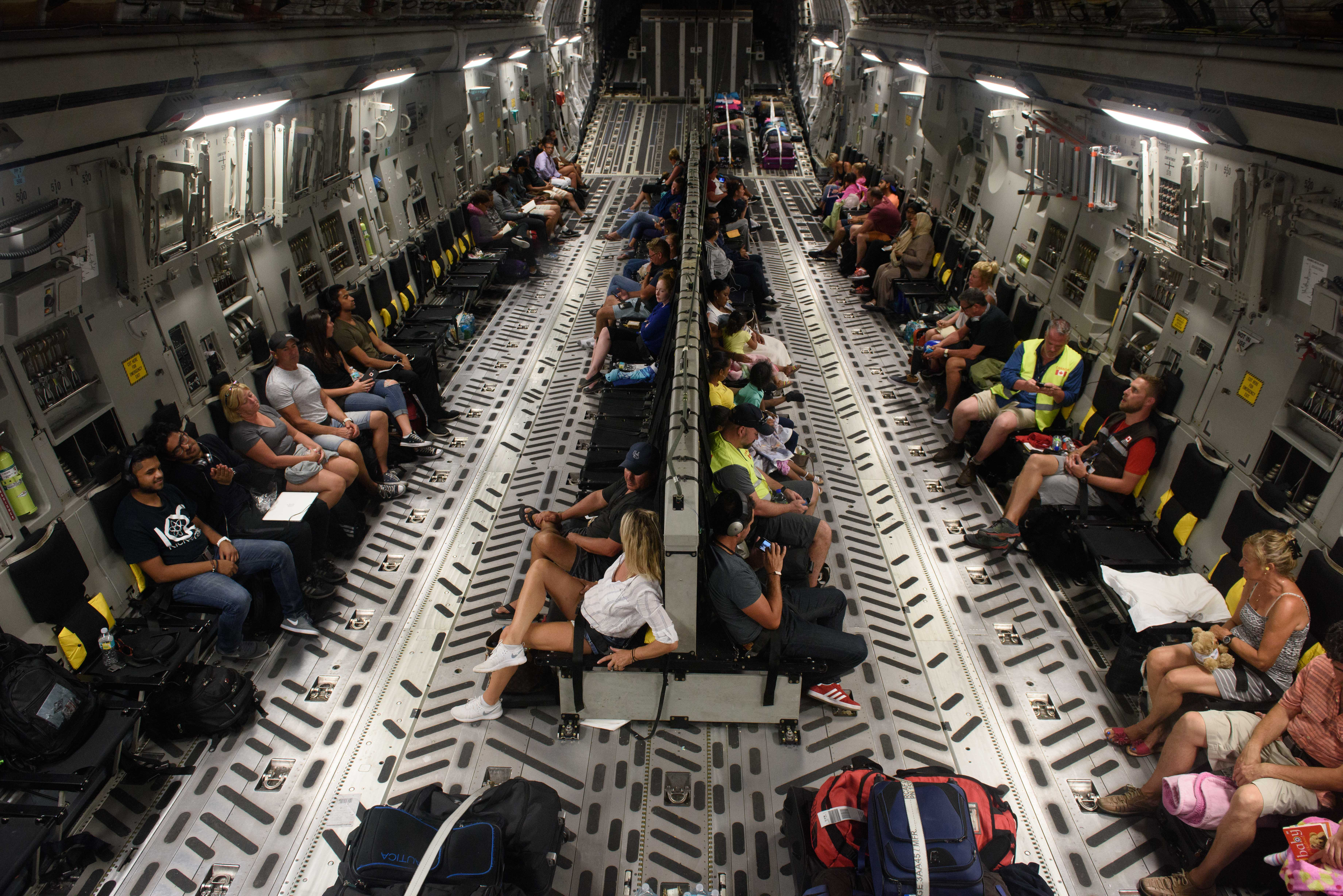 Fifty Canadian citizens stranded in the Caribbean following Hurricane Irma await departure inside a Canadian Air Force CC-177 Globemaster departing from the Provindeciales airport in the Turks and Caicos as part of Operation RENAISSANCE, September 14, 2017. Photo: MCpl Louis Brunet, Canadian Air Force Public Affairs