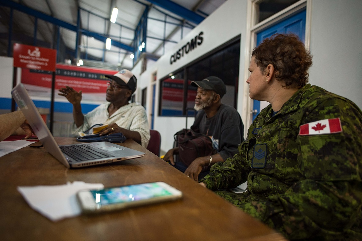 Sergeant Melissa Farrell listens to a couple of Canadian refugees coming from the island of Dominica, talking about their experience after Hurricane Maria, at the port in St. Lucia, in the Caribbean, September 23, 2017. Photo: Corporal Gary Calvé, Imagery Technician, ATF RENAISSANCE.