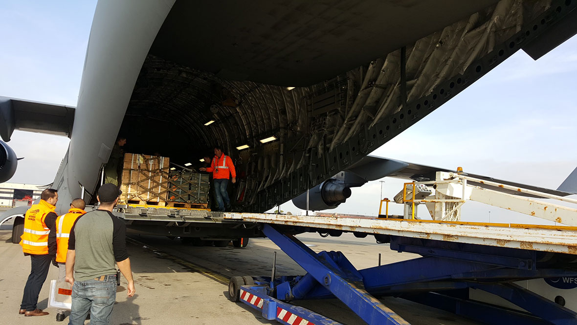 Three men watch while cargo is loaded into the back of a plane
