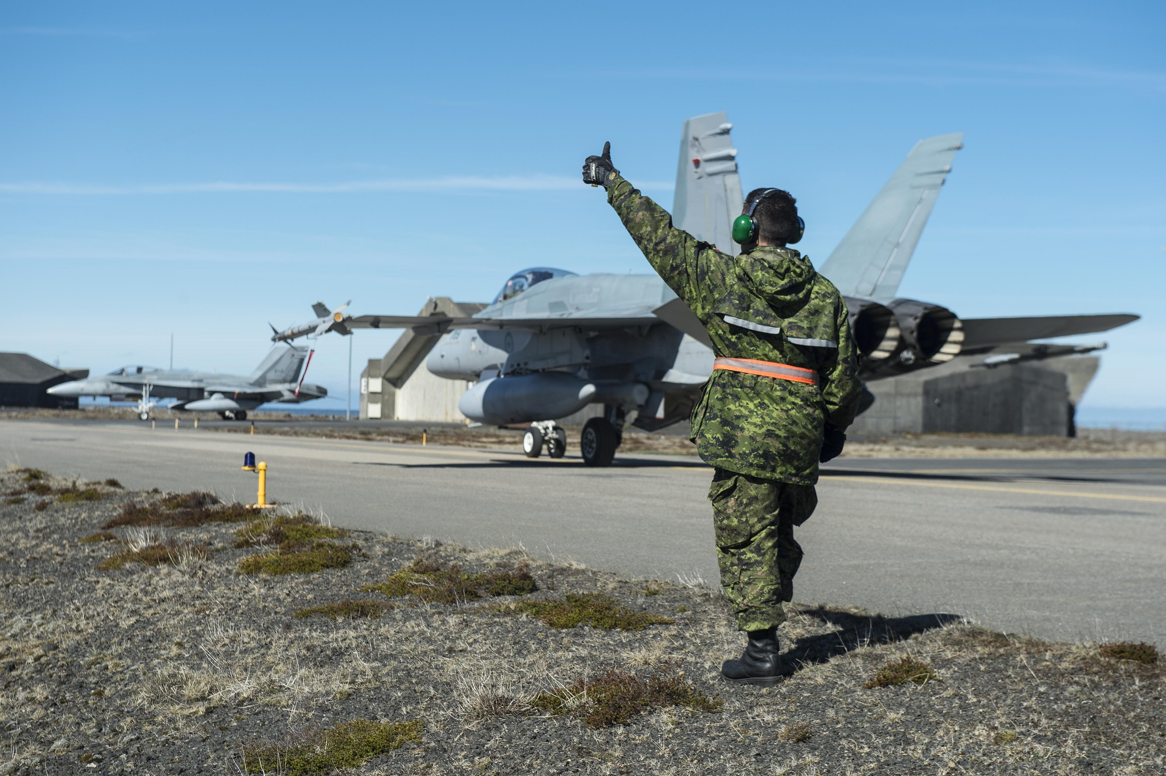19 May, 2017. Weapons technician, Corporal Chad Doley-Bourger, signals that the CF-188 is disarmed and ready to return to the hangar during op REASURANCE, Keflavik, Iceland on 19 May, 2017. (Photo: Cpl Gary Calvé. Image technician ATF-Iceland)