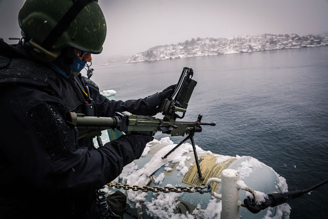 A Royal Canadian Navy (RCN) member currently deployed on board Her Majesty's Canadian Ship (HMCS) St. John's inspects the C-9 Light Machine Gun after departing Bergen, Norway during Operation REASSURANCE on February 12, 2018. Photo: Corporal Tony Chand, Formation Imaging Services