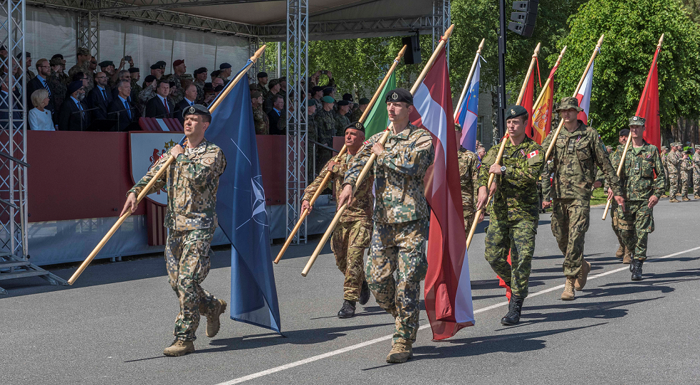 June 19, 2017. Soldiers from the six contributing nations and Latvia march their flags proudly behind the NATO flag during the ceremony that marks the standup of the enhanced Forward Presence Battlegroup Latvia at Camp Ādaži, Latvia on June 19, 2017. (Photo: MCpl True-dee McCarthy, Canadian Forces Combat Camera)