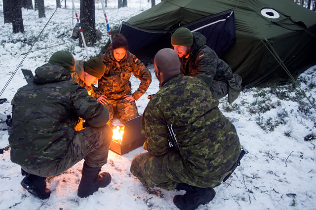 A Canadian soldier demonstrates the proper techniques for lighting a portable stove to Spanish soldiers of the enhanced Forward Presence Battle Group Latvia during Winter Warfare training in the Camp Ādaži training area during Operation REASSURANCE on January 31, 2018. Photo: Cpl Jean-Roch Chabot, eFP BG LATVIA PUBLIC AFFAIRS