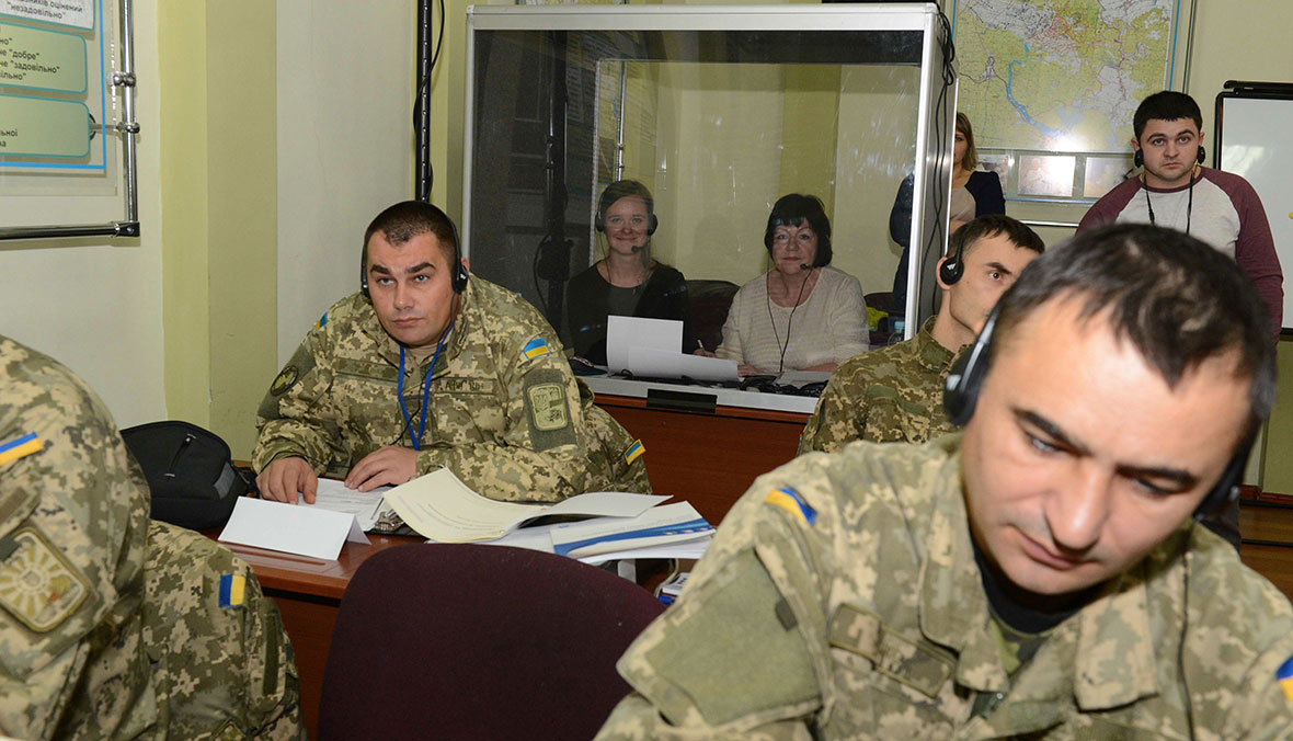 Ukrainian military members sit at desks and write notes