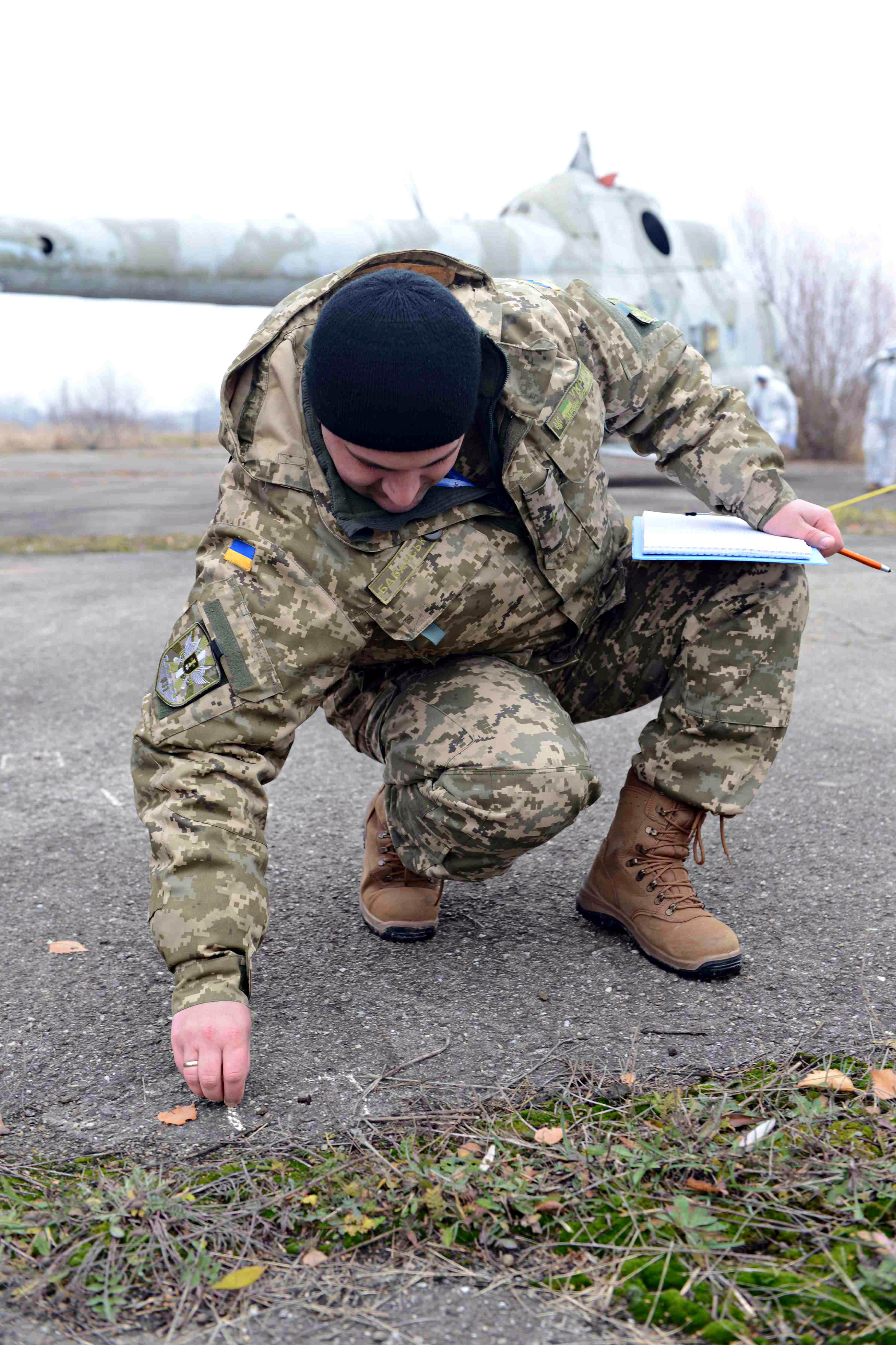 A student from the Flight Safety Course on Operation UNIFIER examines debris while conducting the survey of a simulated helicopter crash site during an exercise at the Lviv Airport military complex in Lviv, Ukraine, on November 22, 2016. (Photo : Joint Task Force – Ukraine)