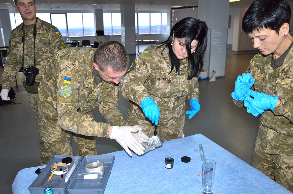 Military members wearing gloves gathered around a table with crime investigation tools.