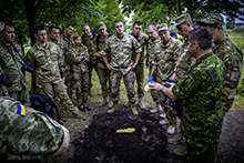 ak51-2016-59-003 July 21 2016. Ukrainian Armed Forces (UAF) assistant instructor, Major Onipko, stands surrounded by UAF students as trainees as a Canadian Military Police Instructor explains the technique of footprint casting during the Canadian led Military Police Investigator Course in Kyiv, Ukraine as part of Operation UNIFIER, on the 21st of July, 2016. (Photo: Joint Task Force Ukraine)