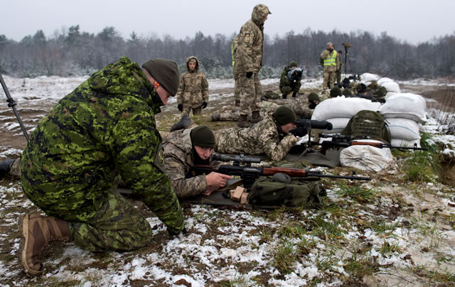 A Canadian Armed Forces infanteer from the Joint Task Force – Ukraine advises members of the Ukrainian Armed Forces on marksmanship principles on a range at the International Peacekeeping and Security Centre located near Starychi, Ukraine during Operation UNIFIER on November 27, 2017.        Photo: Corporal Andrew Kelly, Canadian Forces Combat Camera