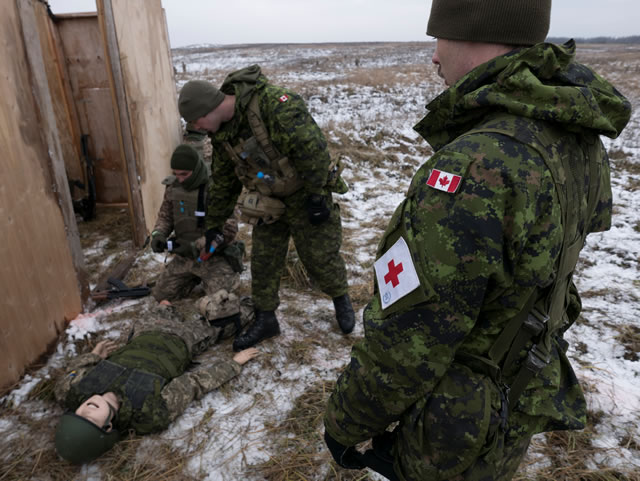 Canadian Armed Forces medics observe Ukrainian soldiers who practice combat first aid skills during a dry-fire exercise near Starychi, Ukraine during Operation UNIFIER on November 29, 2017.                                        Photo: Capt Thomas Edelson, Canadian Forces Combat Camera