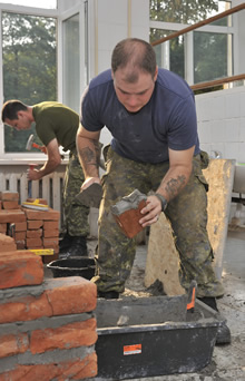 Yavoriv, Ukraine. 15 August 2015 – A member of the Canadian Armed Forces Theatre Activation Team (TAT) lays brick for new shower stalls in the accommodations to be used by Joint Task Force Ukraine members at the International Peacekeeping and Security Centre (IPSC) in Yavoriv, Ukraine during Operation UNIFIER on August 15, 2015. (Photo: OP UNIFIER – DND, Joint Task Force Ukraine)