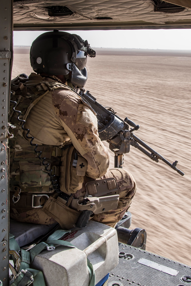 A door gunner with the Tactical Aviation Detachment watches out of a CH-146 Griffon helicopter during Operation IMPACT on September 27, 2017. Photo: Op IMPACT, DND