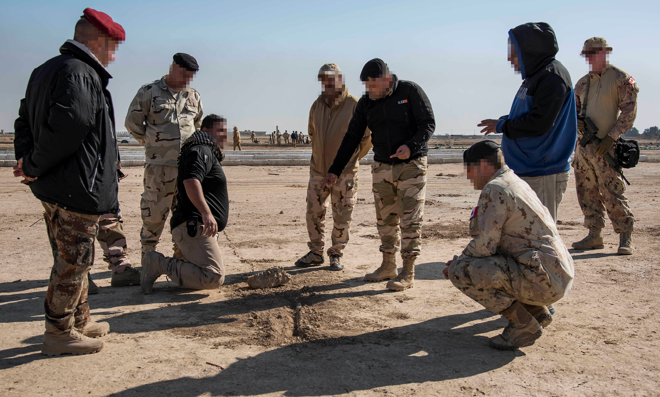 Photo has been digitally altered for operational security. A Royal Canadian Engineer from the Explosive Threat Training Team (ET3) (third from the right) observes an Iraqi soldier (fourth from the right) as he teaches other Iraqi soldiers on how to deal with an Improvised Explosive Device (IED) during Operation IMPACT on November 28, 2017. Photo: Op Impact, DND