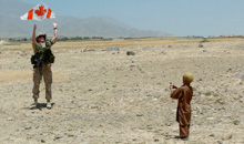 Kabul, Afghanistan. 27 June 2004- Major Richard Sneddon of the Royal 22e Régiment from Valcartier, Quebec, commandant of the Canadian civil-military co-operation team, helps an Afghan boy get his kite into the air. (Photo: MCpl Yves Proteau)