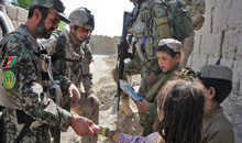 Panjwa'i District, Afghanistan. 23 June 2011- Royal 22e Régiment, Bravo Company, second in command, Captain Patrick Chartrand and Afghan National Army, Second Company, Platoon Commander, Lieutenant Sayed Khan distribute school supplies to Afghan children in the village of Small Loi Kola. (Photo by: Sergeant Matthew McGregor, Canadian Forces Combat Camera)