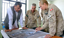 Kandahar, Afghanistan. 3 July 2011- Governor of Kandahar Province, Tooryalai Wesa, Task Force Kandahar Deputy Commanding Officer, Colonel Richard Giguère, and Task Force Kandahar Engineering Squadron Officer Commanding, Major Barbara Honig review a map of the Daman District area to see what improvements have been completed. (Photo by: Sergeant Matthew McGregor, Canadian Armed Forces Combat Camera)