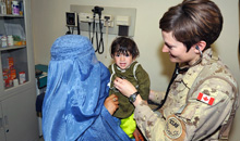 Kandahar, Afghanistan. 02 March 2010- Canadian Forces Medical Officer, Lieutenant (Navy) Kirsten Barnes uses her stethoscope to perform a check up on a young Afghan child. (Photo : Master Corporal Matthew McGregor, Image Tech, JTFK Afghanistan, Roto 8)