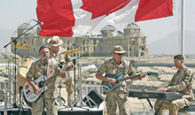 Kabul, Afghanistan. 21 May 2004- Lead singer Sgt Fred Caron, MBdr Yann Carpantier (drums), Cpl Martin Pelletier (guitar), and Pte Benoit Charbonneau (keyboards), perform at Camp Julien in front of the ruins of the King's Palace in Kabul, Afghanistan. (Photo: Sgt Frank Hudec, Canadian Armed Forces Combat Camera)