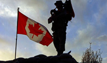 Kabul, Afghanistan. 1 November 2005- As the sun sets Corporal (Cpl) Michael Meagher pipes down the Canadian Flag that is flying over a Forward Operating Base somewhere in Afghanistan. (Photo: Master Corporal Ken Fenner, Task Force Afghanistan, Roto 0 Photographer)