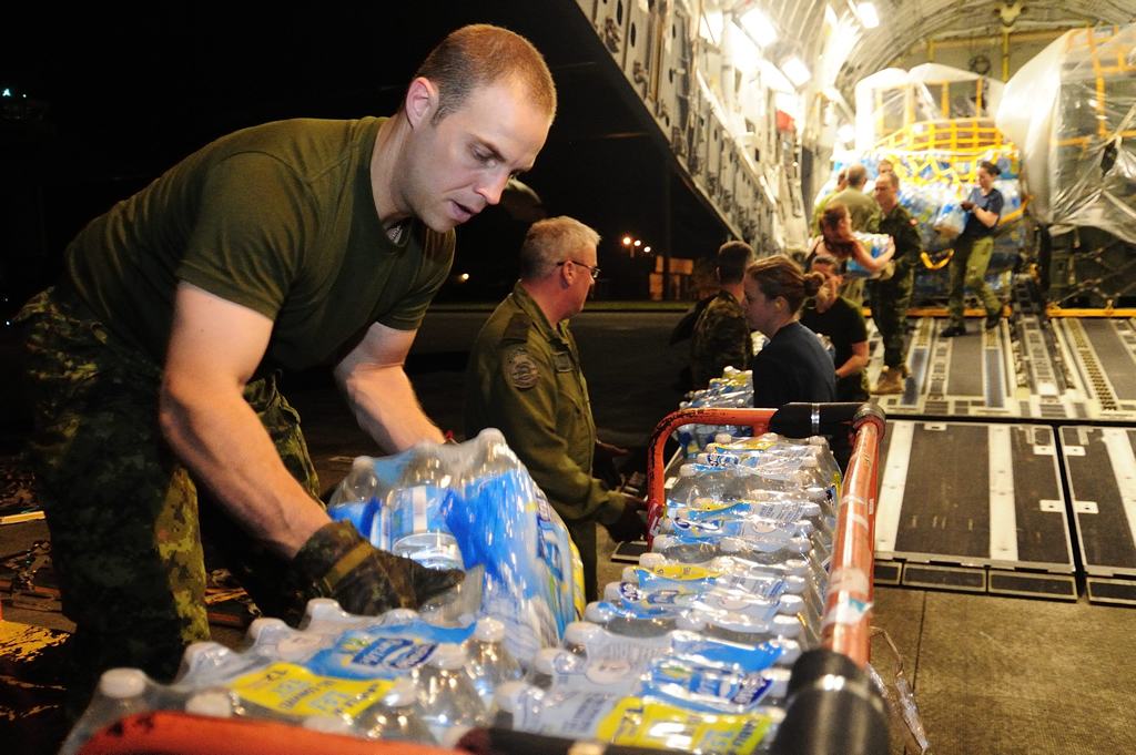 Iloilo, Philippines; 14 November 2013 – Captain Eric St.Jean and members of the CC-177 Globemaster, 2 Air movement squadron and other member of the Disaster Assistance Response Team (DART) off load water on 14 November 2013. Captain St.Jean and the others are deployed in the Philippines to assist the country devastated by Typhoon Hailan, one of the largest typhoons on record. (Photo IS2013-6006-01 by Corporal Darcy Lefebvre, Canadian Forces Combat Camera)