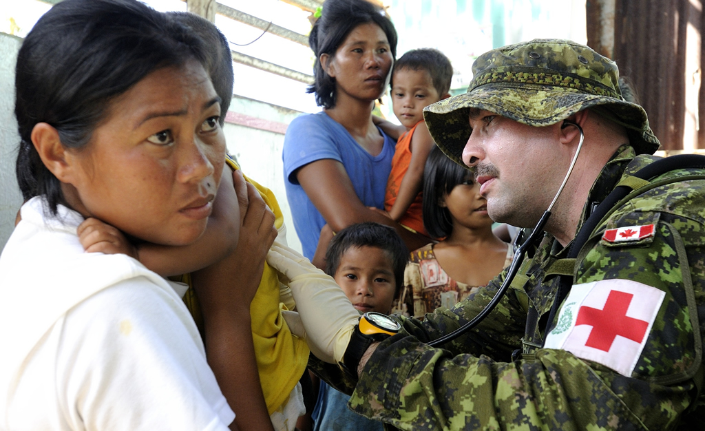A medic checks a child's breathing with a stethoscope