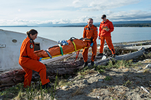 September 14, 2015. Search and Rescue Technicians Master Corporal Ashley Barker (left) and Master Corporal Jeff Connors with 413 Squadron from 14 Wing Greenwood, move a casualty to a safe location while exercise evaluators keep watch, during a medical event as part of SAREX 15, in Comox, British Columbia on September 14, 2015. (Photo: Corporal Ian Thompson, Imagery Technician, 4 Wing Cold Lake AB)