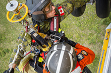 June 2, 2016. Sergeant Chad Hildebrandt, Search and Rescue Technician with 442 Transport and Rescue Squadron hoists Corporal Ryan Morris, student from the Canadian Forces School of Search and Rescue Technician Course 49, to a CH-149 Cormorant helicopter during the final operations phase of the course, in Jarvis Lake, Alberta,  June 2, 2016. (Photo: Corporal PJJ Létourneau, 19 Wing Imaging)