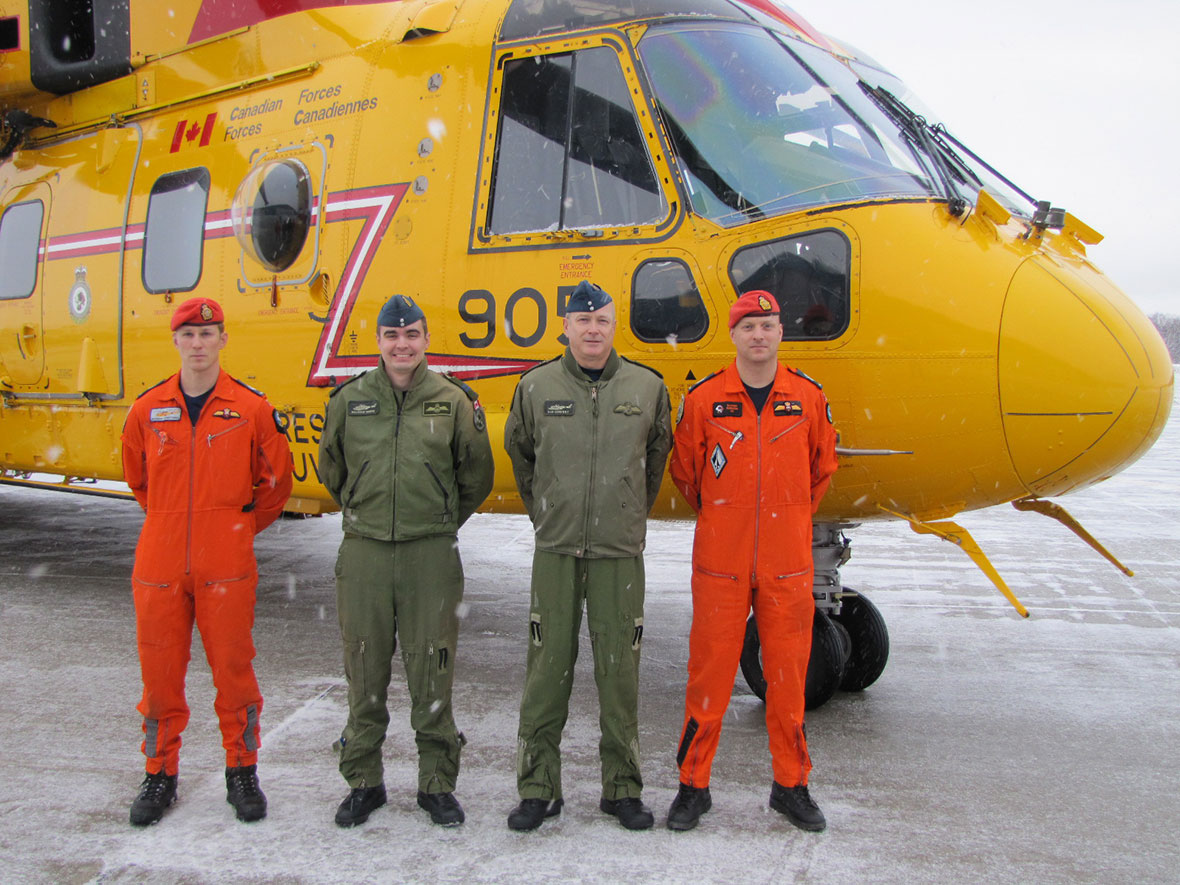 Four men stand in front of a helicopter.