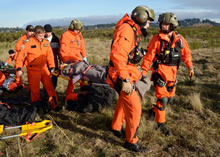 Comox, British Columbia, 22 November 2013 – Search and Rescue Technicians prepare to evacuate a victim of a mock aircraft crash site for an exercise. (Photo by: Cpl Jennifer Chiasson)