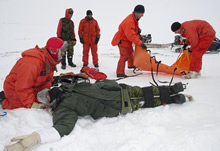 Baring Bay, Nunavut. 22 April 2012 - Sergeant (Sgt) Eric Soubrier, search and rescue technician (SAR tech) stabilizes the mock casualty's neck while SAR techs Sgt Stephane Clavette and Master Corporal Sean Daniell prepare the SKED rescue stretcher/sled at the crash site before transporting him to a warmer location during SAR training, as part of Operation NUNALIVUT 2012. (Photo by Corporal Jax Kennedy, Canadian Forces Combat Camera)