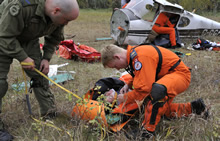 Gimli, Manitoba. 19 September 2013 – Corporal Jason Kennedy (left) and Master Corporal Curtis Schmidt (right) attend to a simulated casualty during the 2013 National Search and Rescue Exercise. (Photo by Darryl Hepner, 17 Wing Winnipeg)