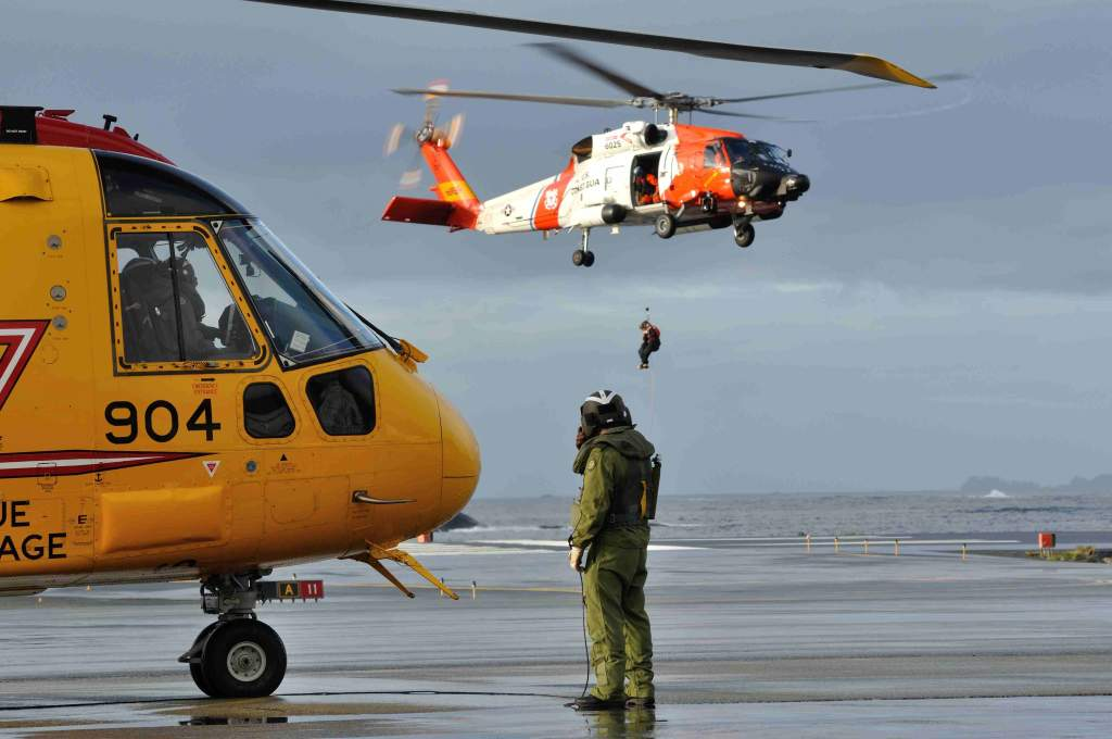 A RCAF engineer prepares a helicopter as a US Coast Guard member is being hoisted in another helicopter in the distance.