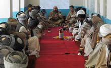 Panjwayi, Afghanistan. 1 November 2007 – Captain Michel Larocque, a Civil-Military Cooperation (CIMIC) Officer for the Provincial Reconstruction Team (PRT) in charge of projects in the Panjwayi District, speaks at a shura to Afghan elders from the area. To his left is Major Patrice Robichaud, Officer Commanding, Charlie Company, 3rd Battalion, Royal 22e Régiment (3 R22eR). The shura, is a meeting of elders in the district, who gather to discuss various issues within the community including topics such as security, growth and development. (Photo by MCpl Robert Bottrill, Canadian Forces Combat Camera)