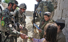 Panjwa'i District, Afghanistan. 23 June 2011 – Royal 22e Régiment, Bravo Company, second in command, Captain Patrick Chartrand and Afghan National Army, Second Company, Platoon Commander, Lieutenant Sayed Khan distribute school supplies to Afghan children in the village of Small Loi Kola. (Photo by: Sergeant Matthew McGregor, Canadian Forces Combat Camera)
