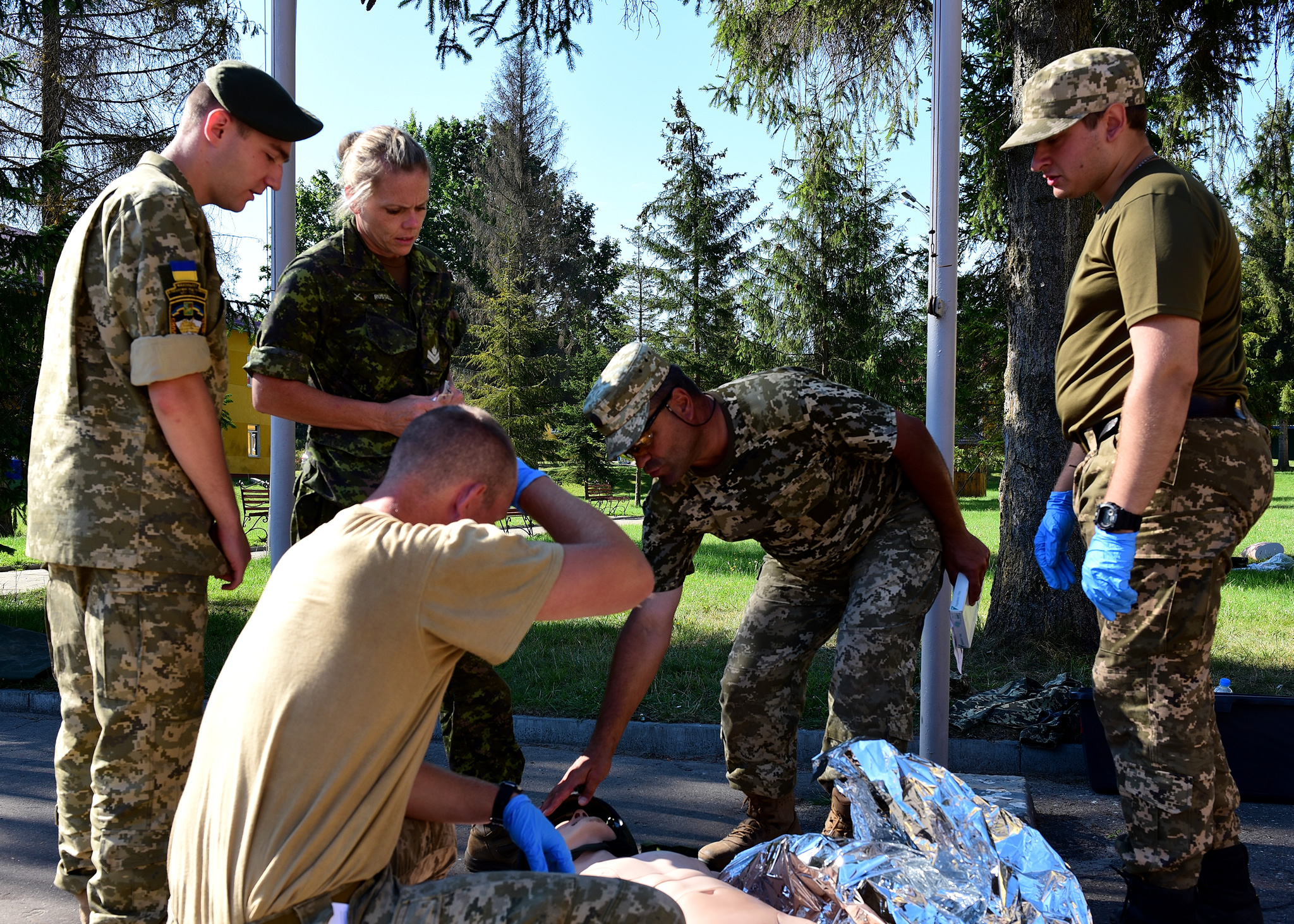 A Ukrainian instructor from the 184th training center supervises and evaluates two of his students, under the watchful eye of master-corporal Jennyfer Russell during a Combat First-Aid Course on Operation UNIFIER on August 3, 2016. The instructor is part of the first group of four Instructor qualified Ukrainians who are teaching the Canadian course to soldiers during the 55 day training block under the supervision of members of Joint Task Force Ukraine. (Photo : Capt J.P. Coulombe, JTF-U PAO)